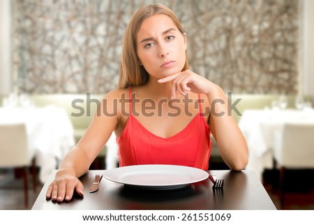 Hungry woman on a diet waiting with an empty plate in a restaurant - stock photo