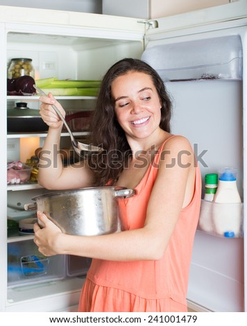 Hungry young brunette woman eating soup from pan near fridge at home - stock photo