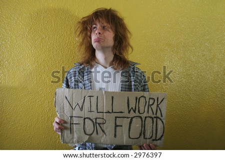 hungry young man holding a cardboard with text