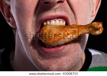 Hungy man eating chicken - stock photo