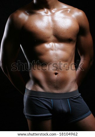 hunky asian young man in boxer trunks and hands behind - stock photo