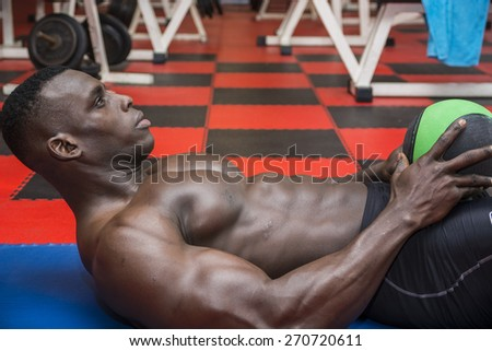 Hunky muscular black bodybuilder working out in gym, exercising abs laying on the floor - stock photo