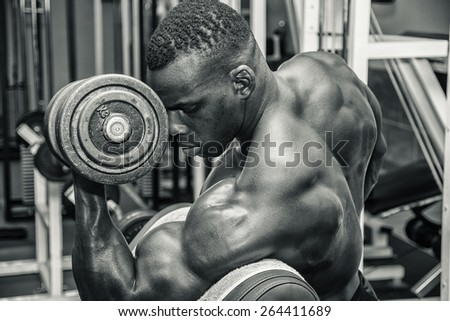 Hunky muscular black bodybuilder working out in gym, exercising biceps with dumbbell. Black and white photo - stock photo