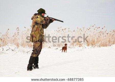 Hunter aiming at the prey, dog waiting for the shotgun to fire. Hunting winter open season scene - stock photo