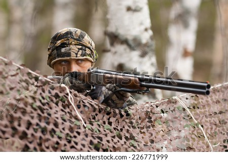 hunter aiming from behind camouflage netting - stock photo