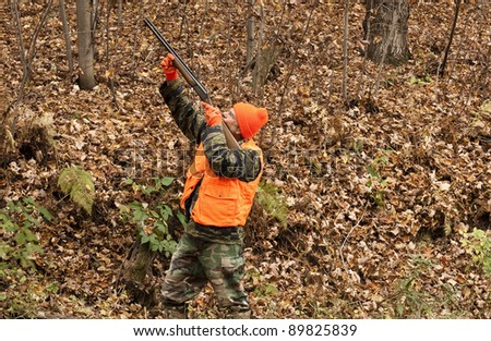 hunter aiming his weapon in the autumn woods