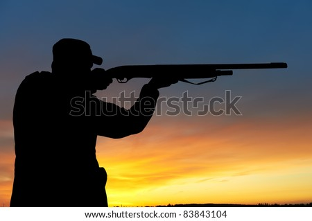 hunter aiming the hunting rifle during a hunt at sunrise - stock photo