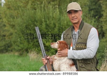 Hunter crouching by dog - stock photo