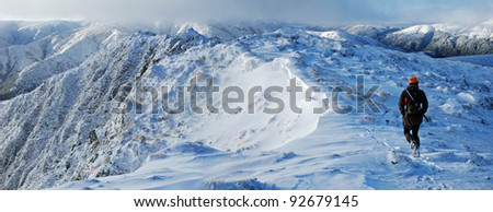 hunter hiking in snowy mountains - stock photo