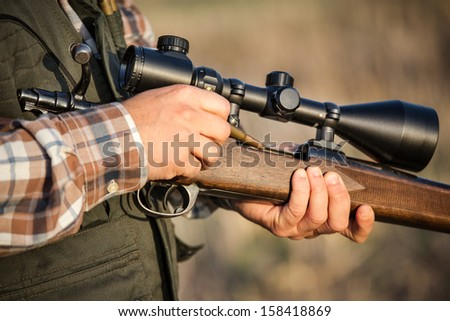 hunter holding a rifle - stock photo