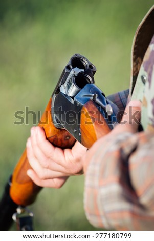 Hunter holding a rifle - stock photo