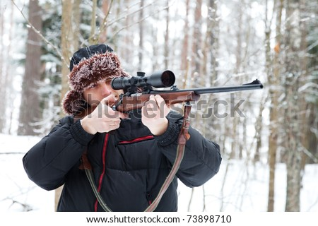 Hunter in a fur cap with ear flaps with sniper rifle in winter forest. - stock photo