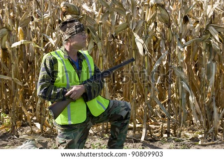 hunter in a safety vest with a shotgun with a corn field    in the background