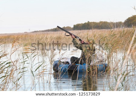 Hunter in an inflatable boat shoots duck - stock photo