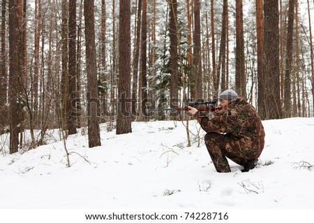 Hunter in camouflage aiming with sniper rifle at winter forest. - stock photo