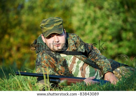 hunter in camouflage clothes lying ready to hunt at forest with hunting rifle
