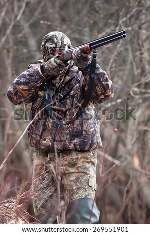 hunter in camouflage shooting from a gun - stock photo