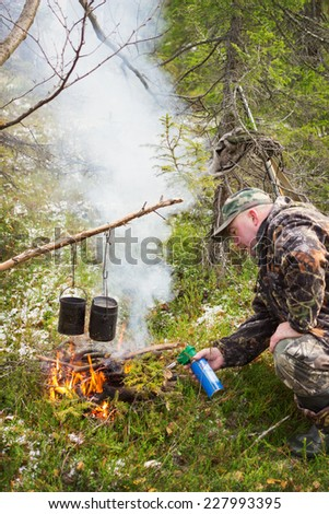 Hunter in forest fire ignites with a gas torch - stock photo