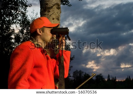 hunter in high visibility clothing looking through binoculars - stock photo
