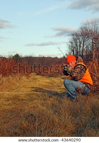 Hunter in orange crouching with shotgun and taking aim - stock photo