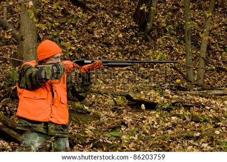 hunter in safety orange aiming shotgun with a fall leaves background