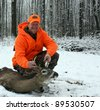 hunter in safety orange with a whitetail deer harvested against a snow and tree background - stock photo
