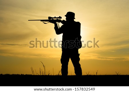 Hunter in the sunset - stock photo