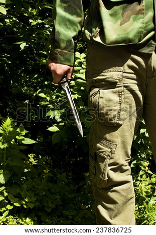 Hunter is holding a knife in his hand at forest - stock photo