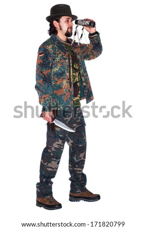 Hunter is holding a knife in his hand while looking through a binocular - isolated on white - stock photo