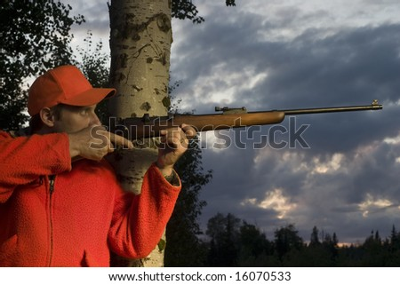 hunter leaning on tree and aiming rifle - stock photo