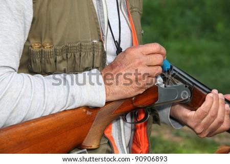 Hunter loading shotgun - stock photo