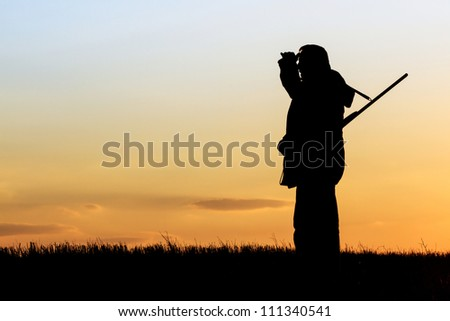 Hunter looking to horizon during a hunt at sunrise - stock photo