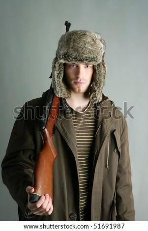 Hunter man fur winter hat holding rifle gun brown autumn coat - stock photo