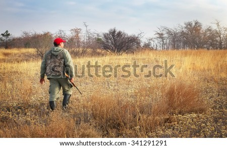 Hunter moving with shotgun looking for prey. Hunter with a gun. Hunting for hare - stock photo