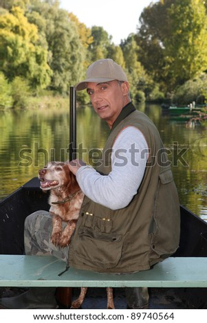 Hunter on a boat with his dog - stock photo