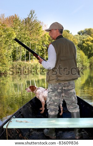 Hunter on boat with dog - stock photo
