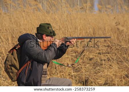 Hunter prepares to shoot wild boar - stock photo