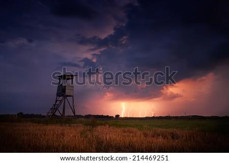 Hunter's ambush in the stormy field - stock photo