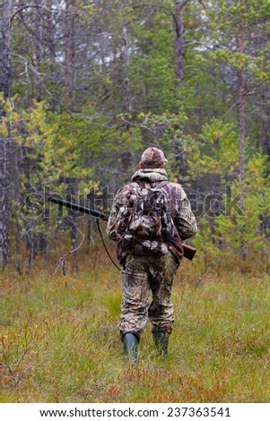 hunter shooting on the forest edge  - stock photo