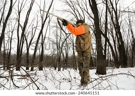 Hunter Shooting Shotgun in Snow - stock photo