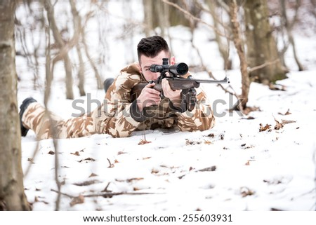Hunter shooting with a sniper rifle, aiming and firing bullets - stock photo