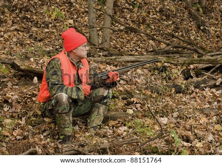 hunter sitting in the autumn woods waiting for game