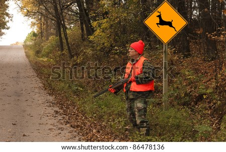 hunter standing by a deer crossing sign waiting for game
