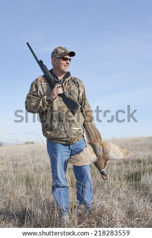 Hunter standing in field holding ring-necked pheasant and shot gun - stock photo