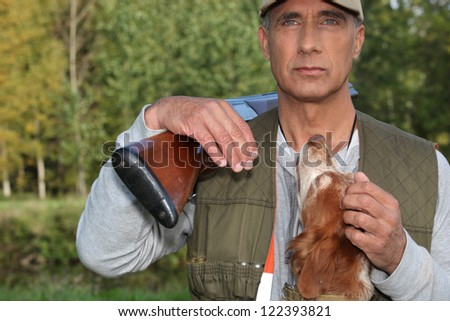 Hunter stroking dog - stock photo