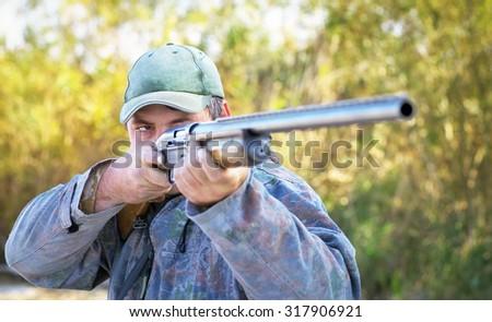 Hunter taking aim at the target. Hunter with a gun. - stock photo