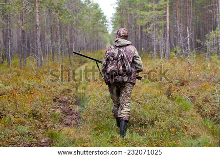 hunter walking on the forest road - stock photo