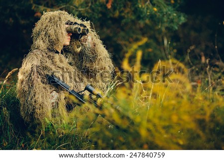 Hunter watching through binoculars purpose - stock photo