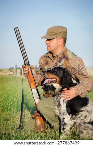 Hunter with a dog on the field - stock photo