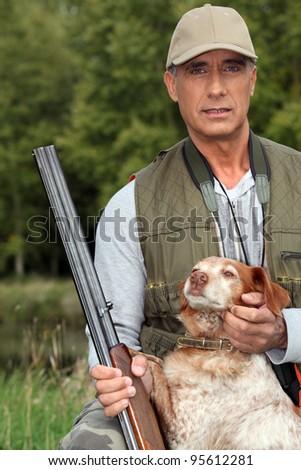 Hunter with a shotgun and dog - stock photo